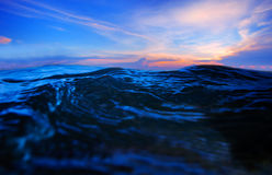 Sea water splashing with dramatic colorful sky in evening royalty free stock image