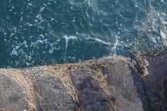 Sea water splashing on the stone steps Royalty Free Stock Photos