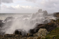 Sea water spray covering rocks from the coast Stock Images