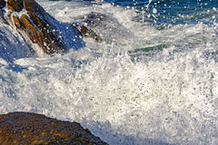 Sea water spray over the stones Stock Image