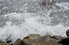 Sea water sprayed on the stone cliff Stock Photo