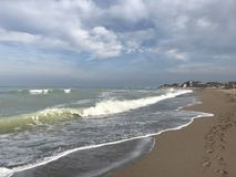 Black sea before storm. Sea water stormy grey clouds storm wet sand wind waves stock image