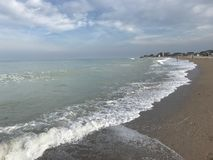 Clouds over black sea. Sea water stormy grey clouds storm wet sand wind waves stock photos