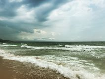 Grey storms over black sea. Sea water stormy grey clouds storm wet sand wind waves royalty free stock photo