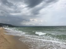 Grey storms over black sea big waves. Sea water stormy grey clouds storm wet sand wind waves stock images