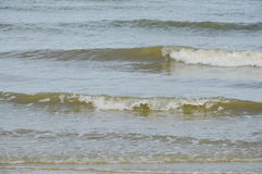 Sea water surf to beach in sunny day Stock Photos