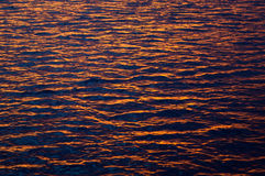 Sea water texture at sunset. Wavy surface of sea water illuminated with dim sunset light stock photo