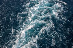 Sea water texture with white foamy wave. Tropical island hopping or marine travel banner. Motorboat trail. Blue ocean top view. Big ship pitching. White water royalty free stock photos
