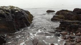 Sea water washing onto rocks on a  sandy beach in Scotland stock video