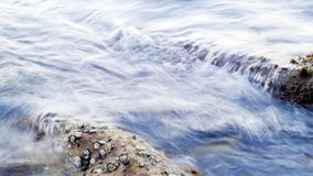 Sea water wave swash to the half-submerged rocks that covered with oysters. Shot with slow shutter speed for water diffuse effect Stock Image