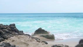 Sea water waves splashing on sandy beach landscape. Turquoise ocean on skyline landscape. Rocks on sandy beach. Sea water waves splashing on sandy beach stock footage