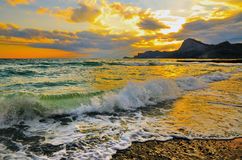 Sea wave on rocky sea coast at sunset stock photos