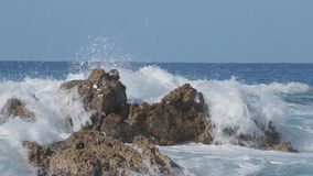 Sea wave beats on a big stone. Sunny day stock video footage