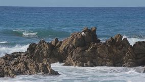 Sea wave beats on a big stones. Sunny day stock video footage