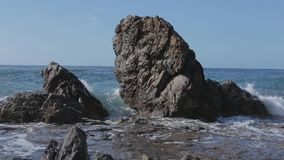 Sea wave beats on a big stones. Sunny day stock video