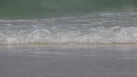 Sea wave in the blue ocean at sun rise in the morning. Bubble foam of the sea wave on the beach and fine sand, the glittering from the bubbles makes the precious stock video footage