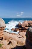 Sea wave breaks against the pink granite rocks Stock Image
