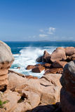 Sea Wave Breaks Against The Pink Granite Rocks Stock Image