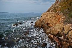 Sea wave breaks on beach rocks landscape. Sea waves crash and splash on rocks at Bodrum, Turkey.  stock images