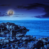 Sea wave breaks about  boulders at night Stock Images