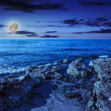 Sea wave breaks about boulders at night Royalty Free Stock Photos