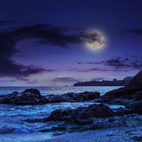 Sea wave breaks about boulders at night Stock Photos