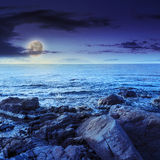 Sea wave breaks about boulders at night Stock Image