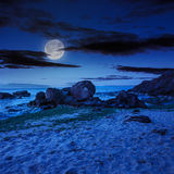 Sea wave breaks about boulders at night Royalty Free Stock Photo