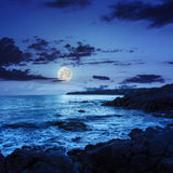 Sea wave breaks about boulders at night. Sea wave attacks the boulders and is broken about them at night in full moon light royalty free stock photography