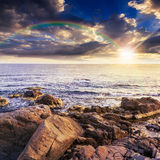 Sea wave breaks about boulders with rainbow Royalty Free Stock Photo