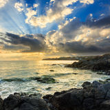 Sea wave breaks about boulders at sunrise. Sea wave attacks the boulders and is broken about them at sunrise stock photos