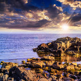 Sea wave breaks about boulders at sunset Stock Images
