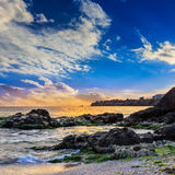 Sea wave breaks about boulders at sunset Royalty Free Stock Photo