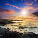 Sea wave breaks about boulders at sunset. Sea wave attacks the boulders and is broken about them at sunset with rainbow royalty free stock photos