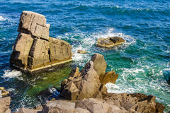 Sea wave breaks about rocky shore. Sea wave attacks the boulders of rocky shore and is broken about them royalty free stock images