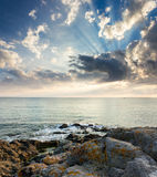 Sea wave breaks about rocky shore at sunrise Stock Photo