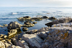 Sea wave breaks about rocky shore at sunrise. Sea wave attacks the boulders of rocky shore and is broken about them on sunrise royalty free stock photos