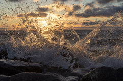 Sea wave breaks about stones, splashes at sunset Stock Photos