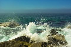 The sea wave is broken on stones, white foam and a spray royalty free stock images