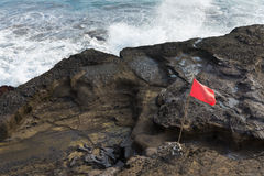 Sea wave coast rock red flag Stock Photo