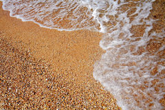 Sea wave covered with foam and sandy coast from above view Royalty Free Stock Images