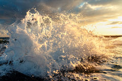 A sea wave crashes into an old breakwater close-up on a background of the setting sun Royalty Free Stock Images
