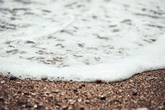 Sea wave foam on beach sand close up Stock Images