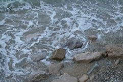 Sea wave with foam beats on the rocks on the shore stock images