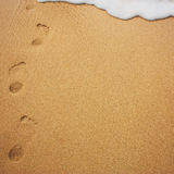 Sea wave with foam and human footprints on sand Royalty Free Stock Photos