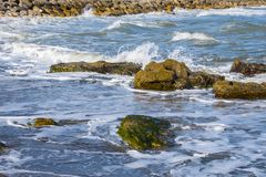 Sea wave foam and rocks on the beach in Estepona, Andalucia, Spain. Peaceful ocean waves at beach.  royalty free stock photo