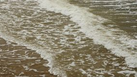 Sea wave foam washing beach on sunny summer day. Sea wave foam washing smooth beach on sunny summer day stock video footage