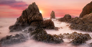 Sea wave hit the rock at sunset Stock Photography