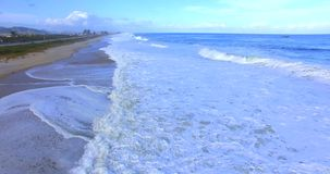 The sea wave. Movement of the camera over the waves. Wave comes close to the shore. 4k video of ocean waves rolling over the coast stock footage