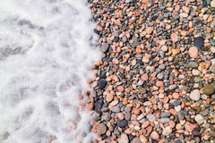 Sea wave on a pebbly beach. Sea foam stock photo